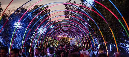 Headliners walking under a colorful archway