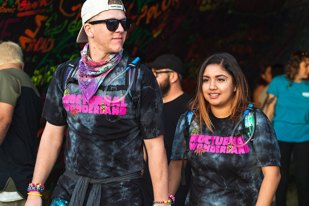 A couple in matching Nocturnal Wonderland T-shirts