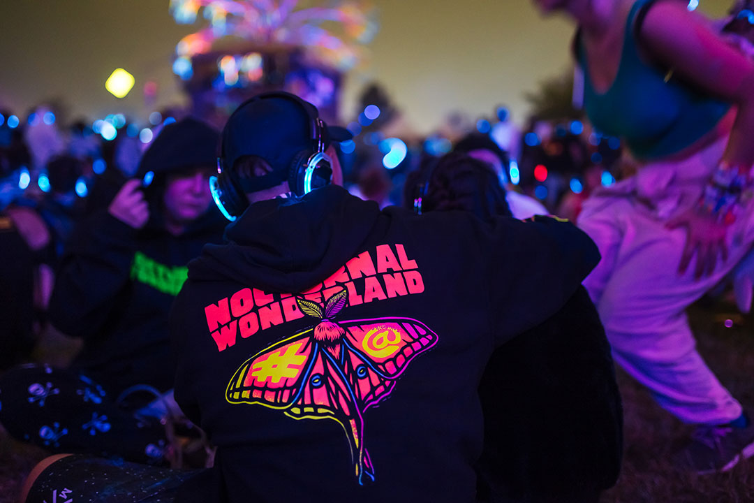 A guy in a Nocturnal Wonderland hoodie at the silent disco
