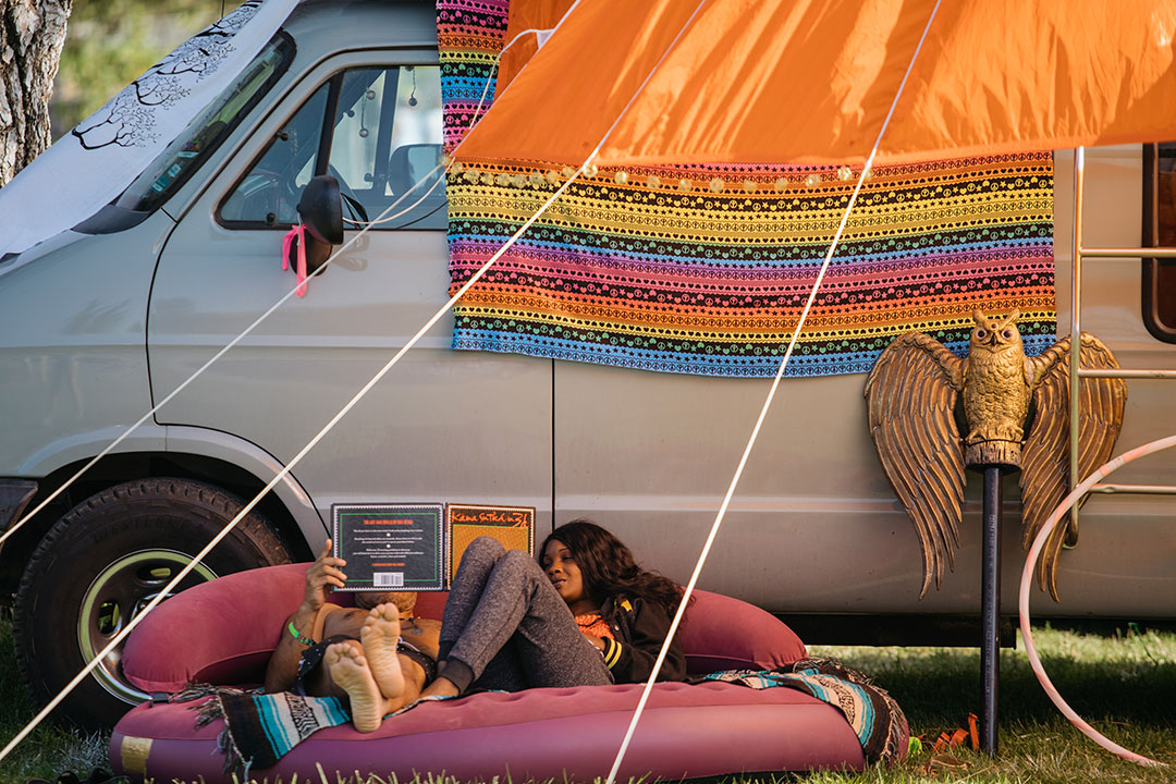 Campers relax under a shade structure