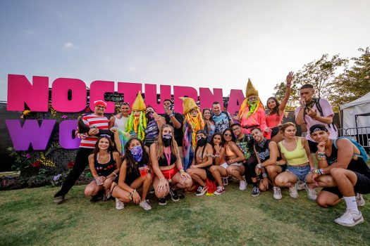Headliners and performers in front of the Nocturnal Wonderland sign