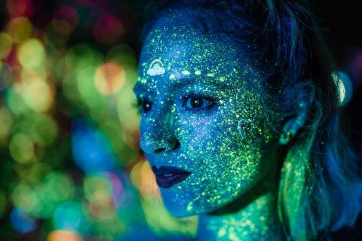 A woman with glow paint on her face