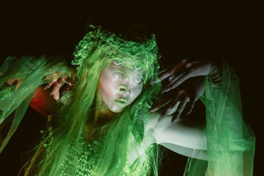 A double-exposed image of a performer in green