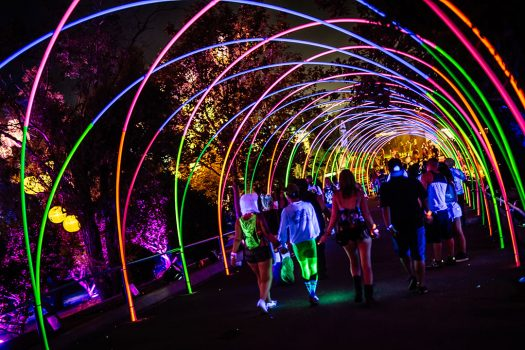 Headliners walk under a glowing archway