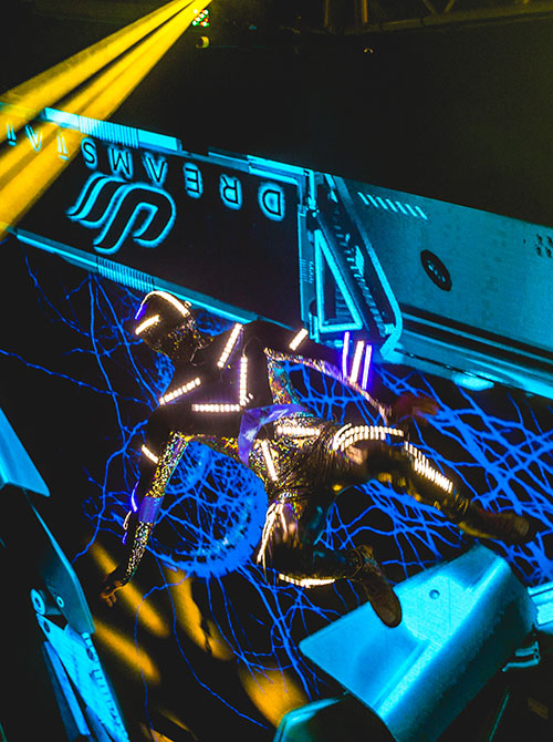 A futuristic performer jumps in the air
