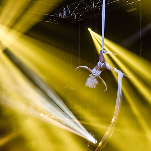 An aerialist performs over the stage
