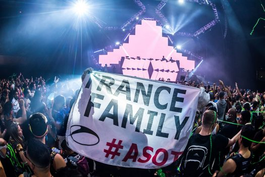 "Headliners hold up a ""Trance Family"" flag"