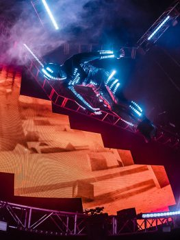 A futuristic performer flips through the air