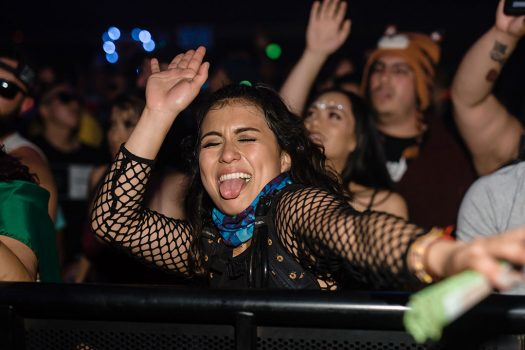 A girl in the front row dancing with her tongue out
