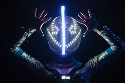A performer in a glowing helmet
