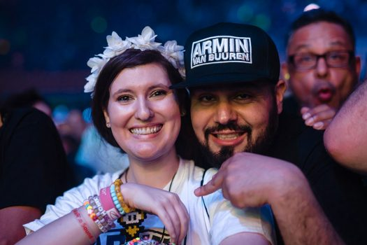 A woman in a flower crown with a man in an Armin van Buuren hat