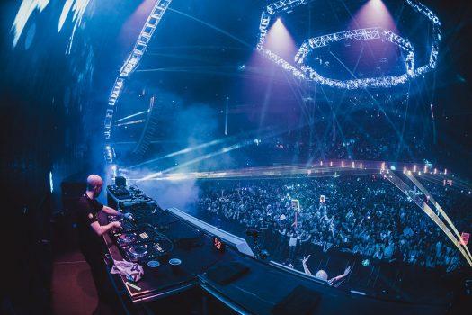 A DJ performs under blue light
