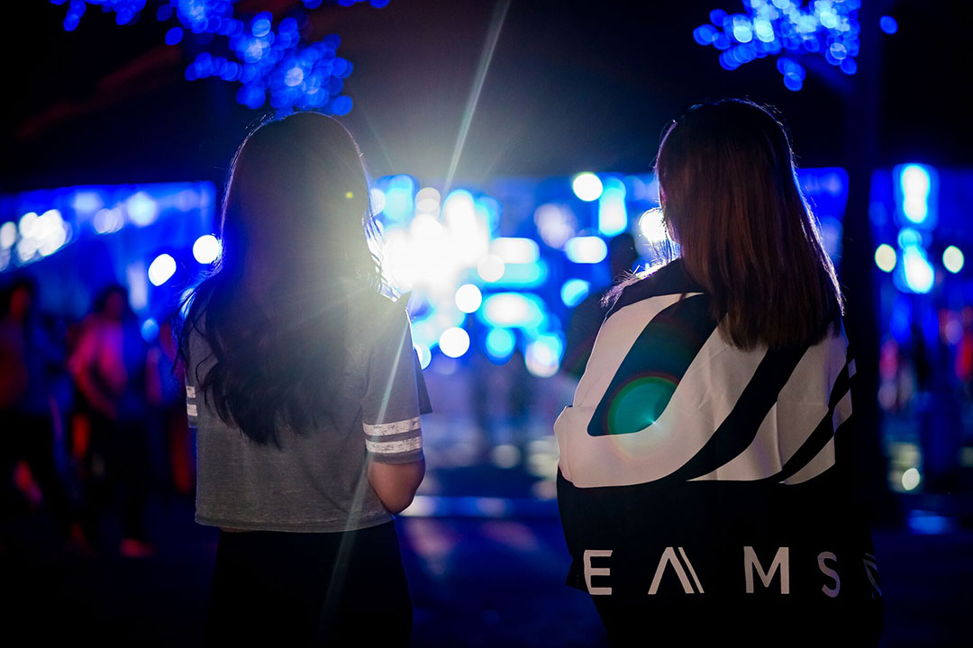 A girl wrapped in a Dreamstate flag stands with her friend