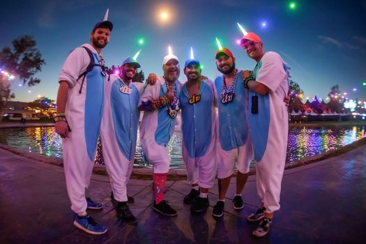 Six men in unicorn hats and onesies