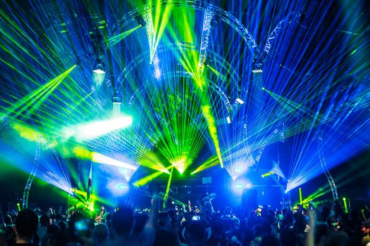 Blue and green lasers shoot from the stage