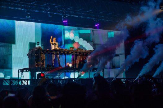 A DJ pumps his fist onstage