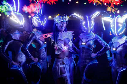 A Headliner poses with costumed performers