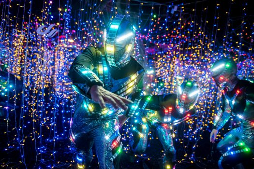 Performers in glowing costumes