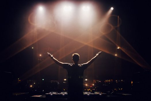 A DJ with his hands in the air