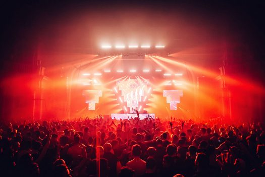 Red lights emanate from the stage