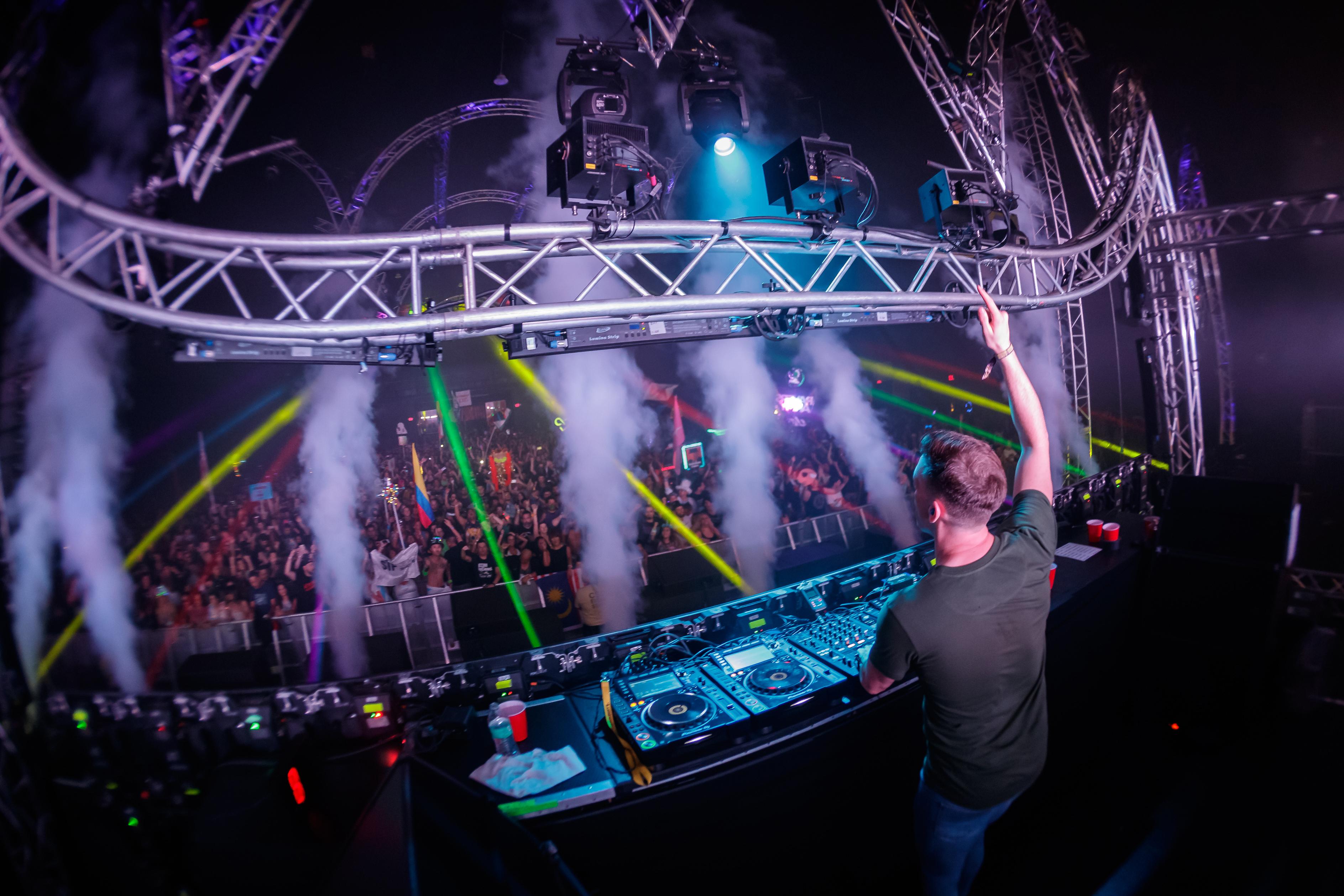 A DJ raises his hand