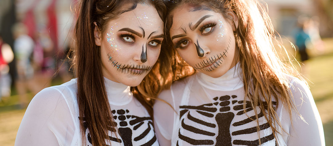 Two women in skeleton costumes