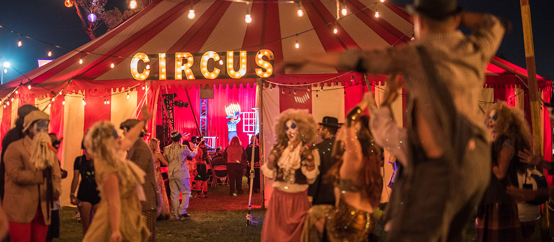 Performers outside a circus tent