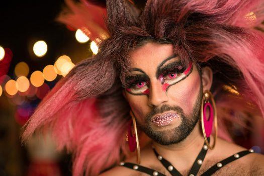 A bearded man in drag makeup