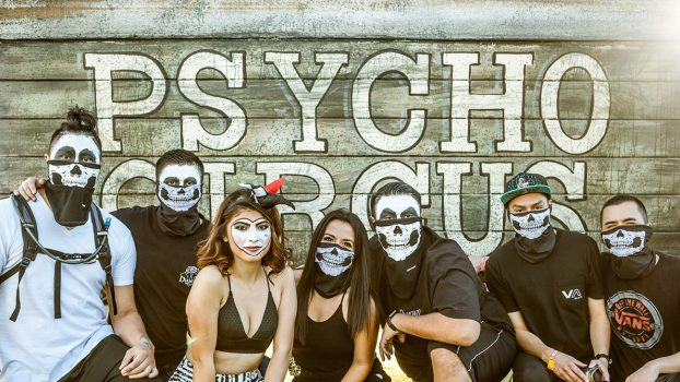 "Masked Headliners in front of a ""Psycho Circus"" sign"