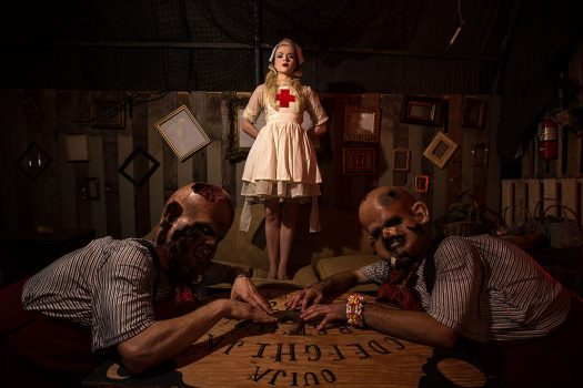 Costumed performers with a Ouija board