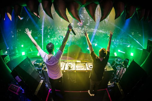 Two DJs with their hands in the air