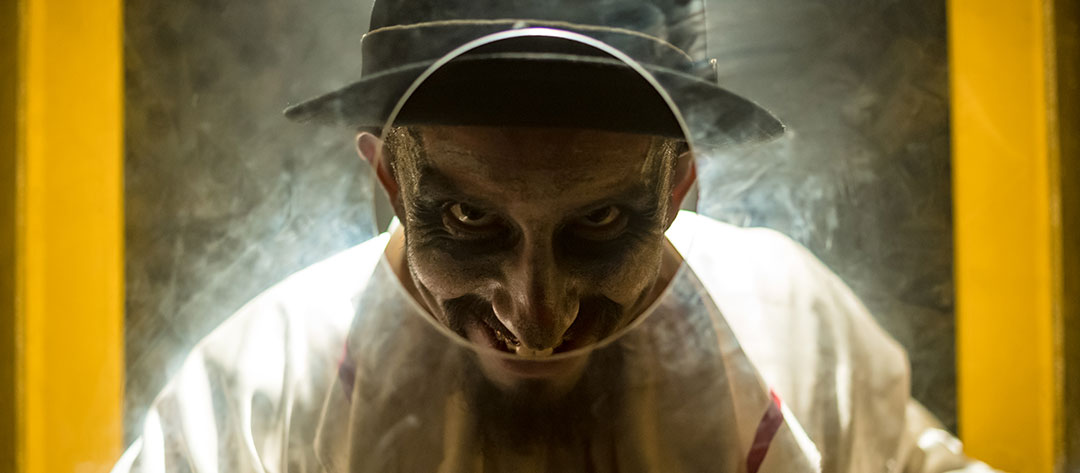 A creepy guy peers through a hole