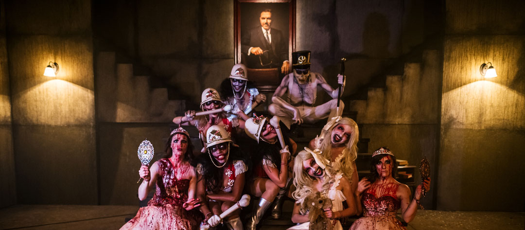 Performers pose in front of a portrait of Pasquale Rotella