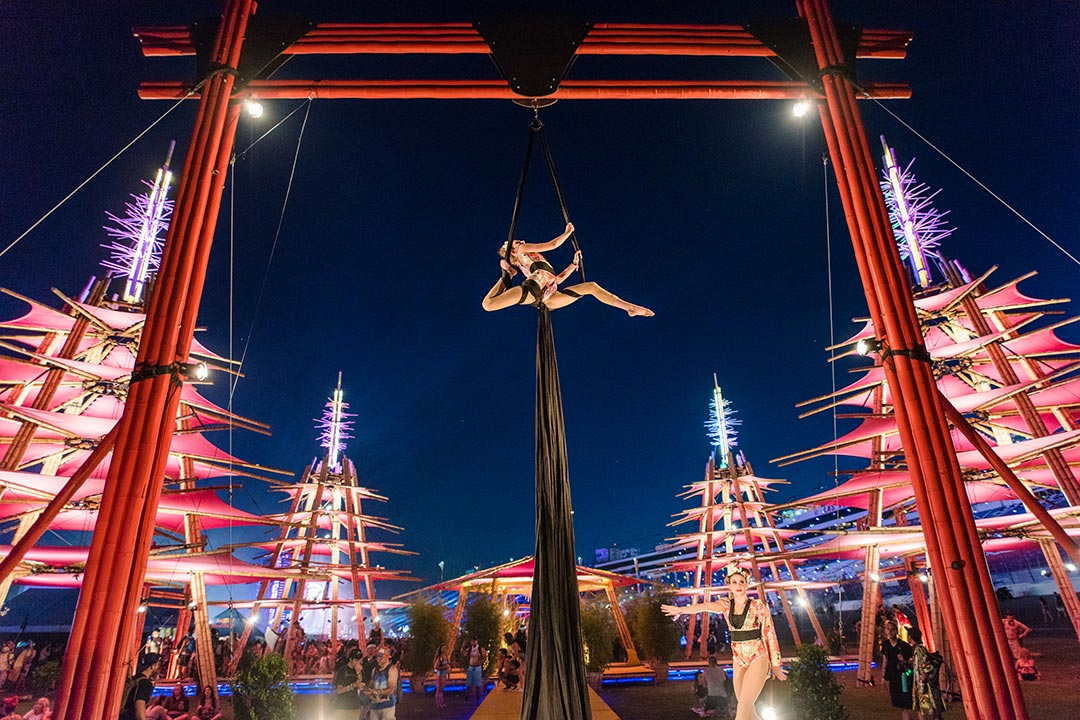 An aerialist at the bamboo temple performs high above a crowd gathered near cosmicMEADOW.