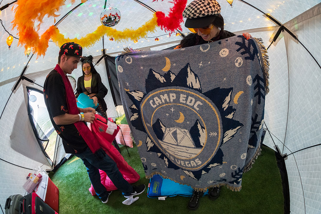 """A Headliner holds up a """"Camp EDC"""" blanket"""