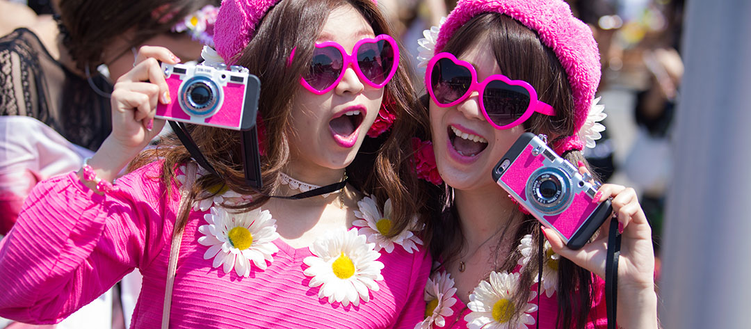 Two girls with heart sunglasses and pink cameras