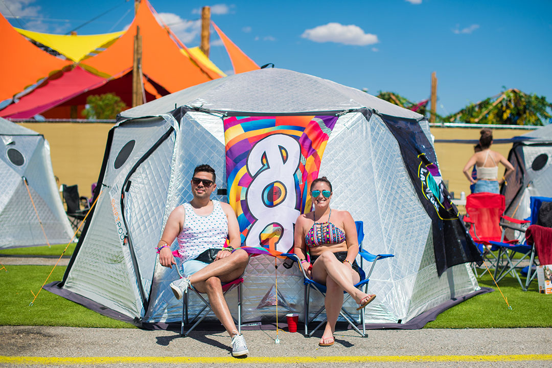 Two people sitting outside their tent