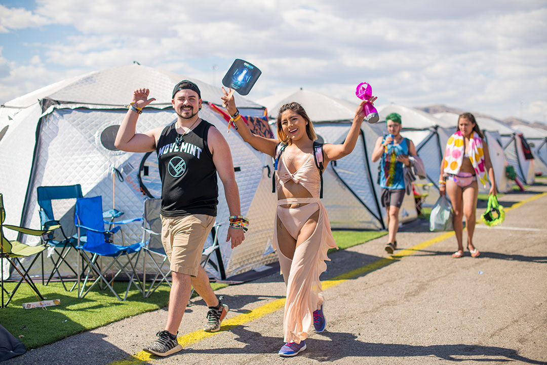Two people walking by the tents