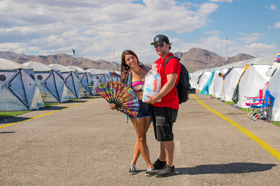Two people standing between rows of tents