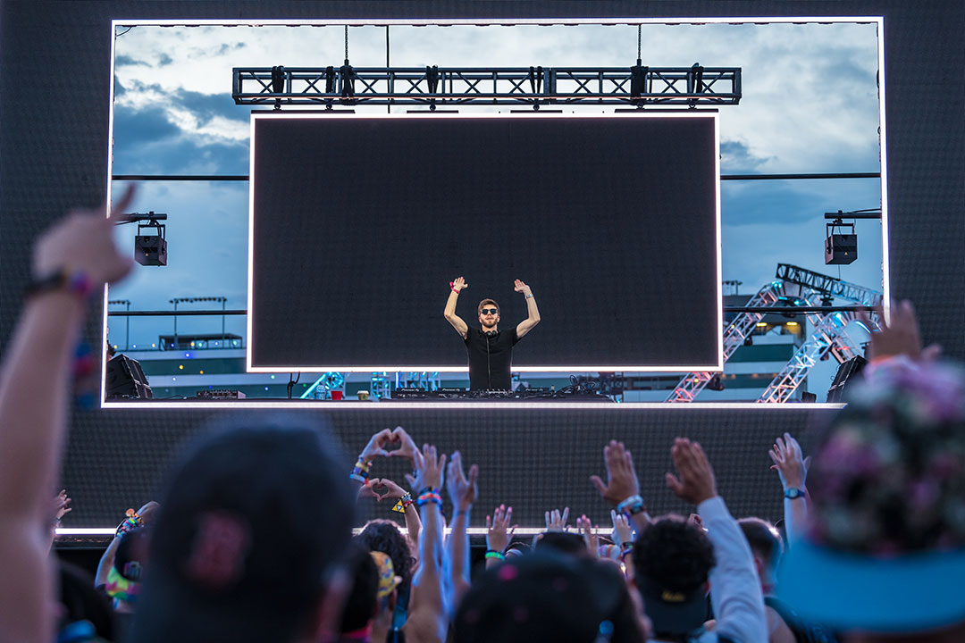 A DJ with his arms up