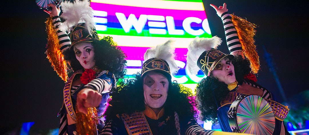 Performers in front of the Welcome sign