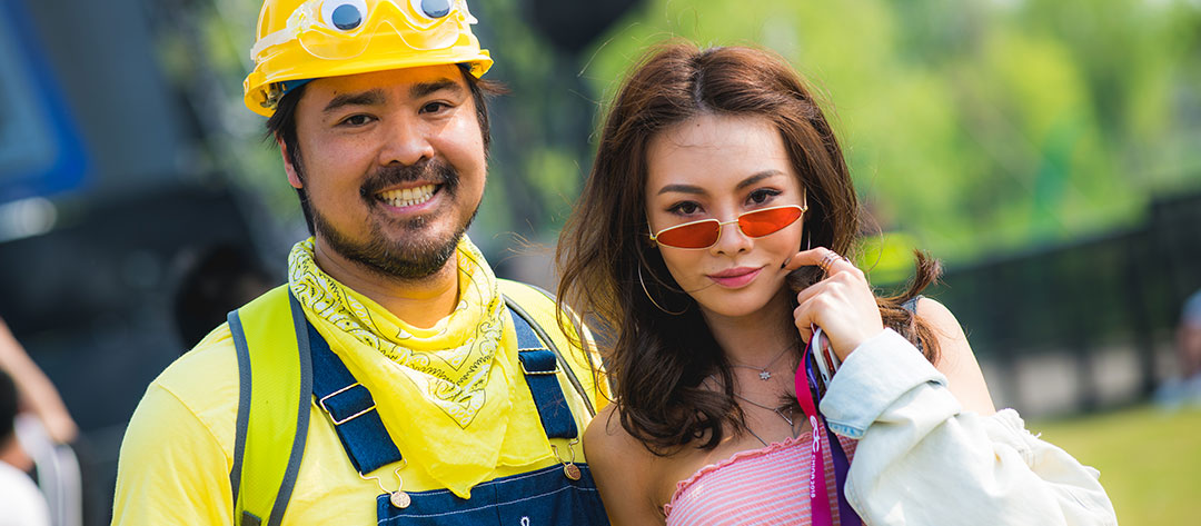 A man in yellow and a woman in sunglasses