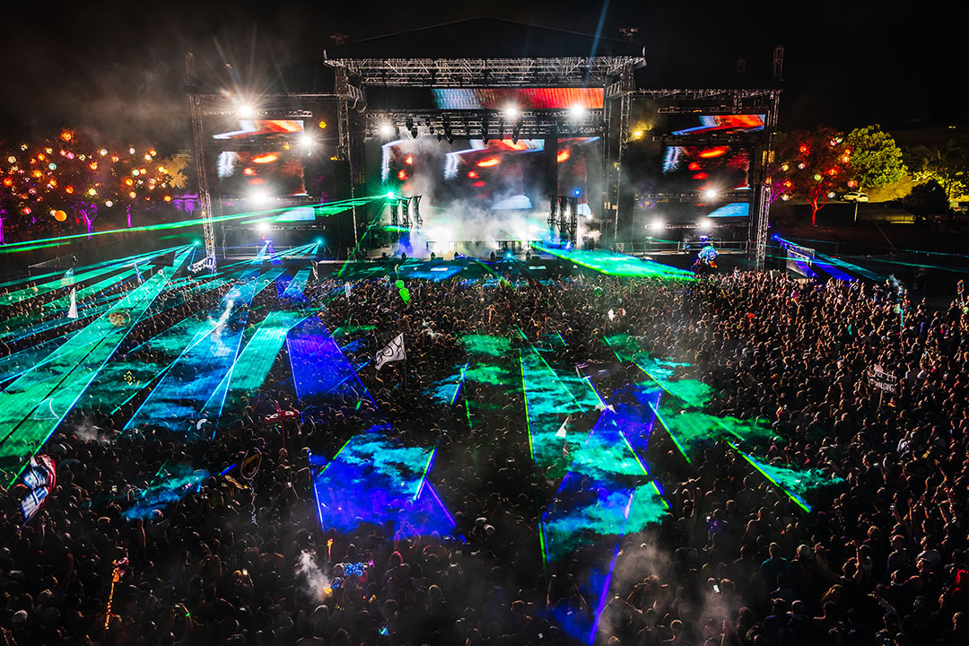 Green and blue lasers shooting over the crowd