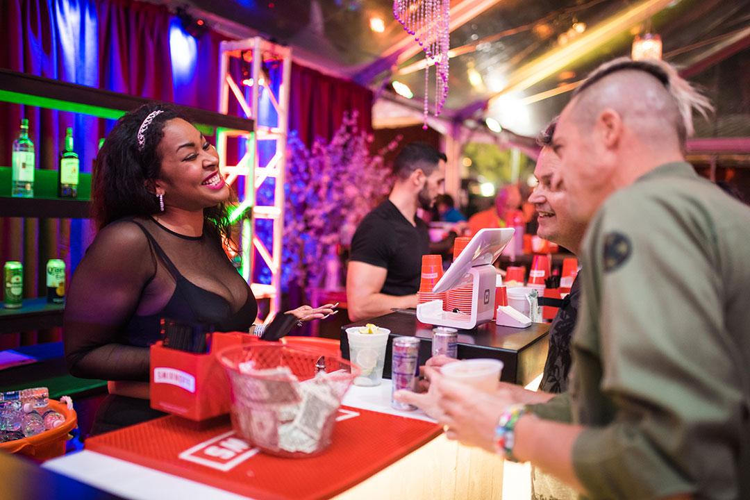 A woman greets people at a bar