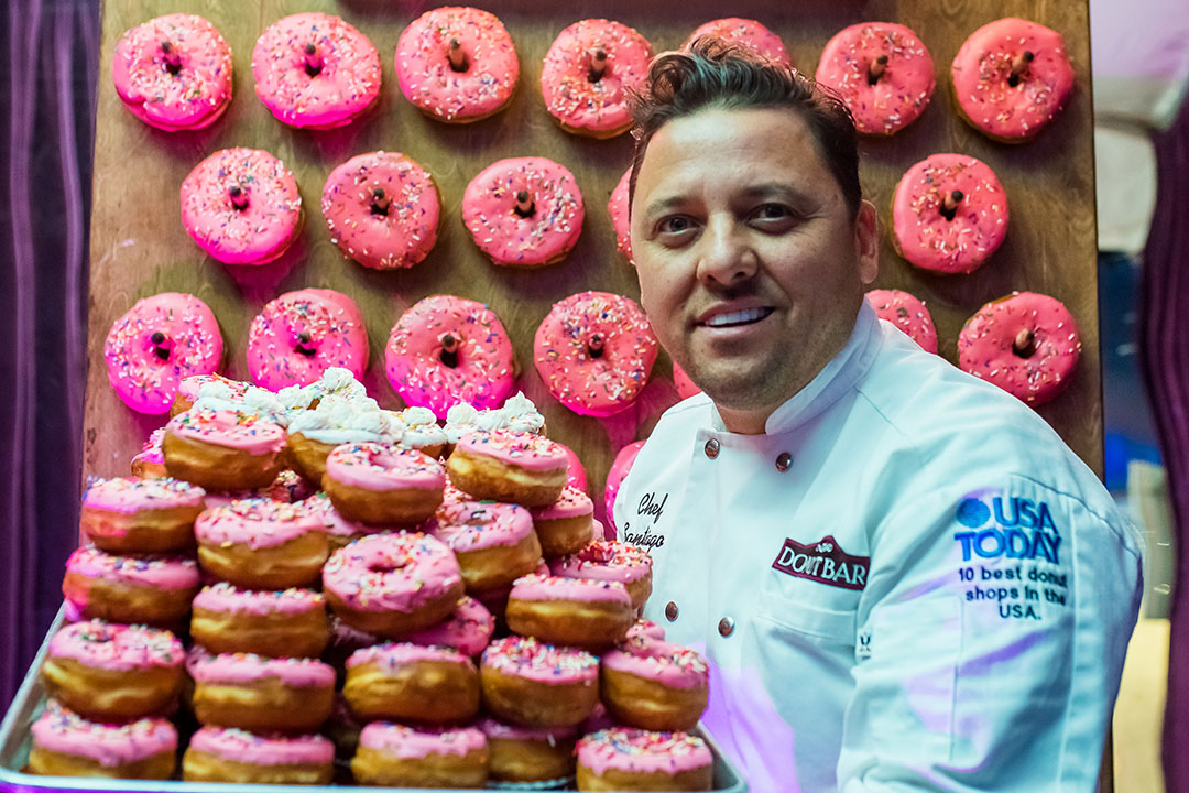 A man with lots of pink donuts