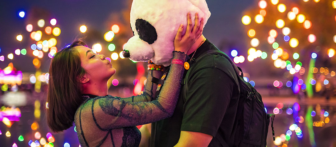 A woman kissing a man in a panda costume