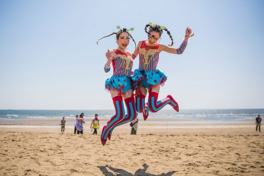 Two dressed-up Headliners jump for joy on the beach at EDC Japan