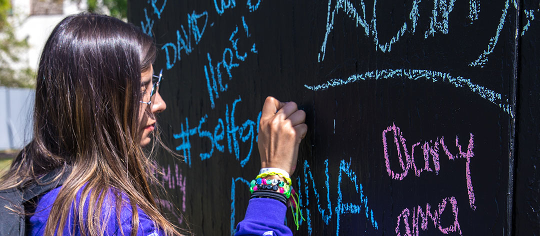 A woman writing on the unity wall