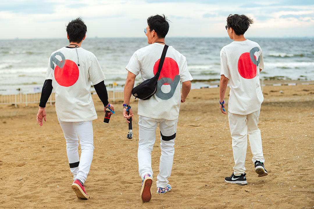 Three guys walk on the beach