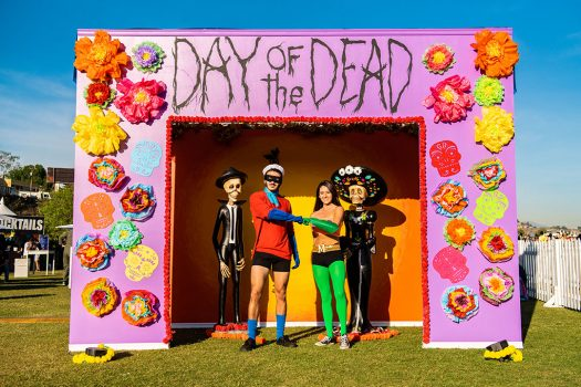 Headliners posing under Day of the Dead sign
